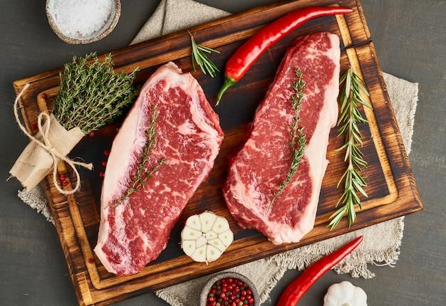 生のステーキを塩、タイム、ニンニクで味付けします。生の牛肉の2つの大きな全体