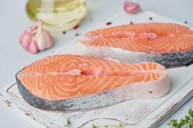 2つの生サーモンステーキ、魚の切り身、テーブルのまな板に大きなスライス