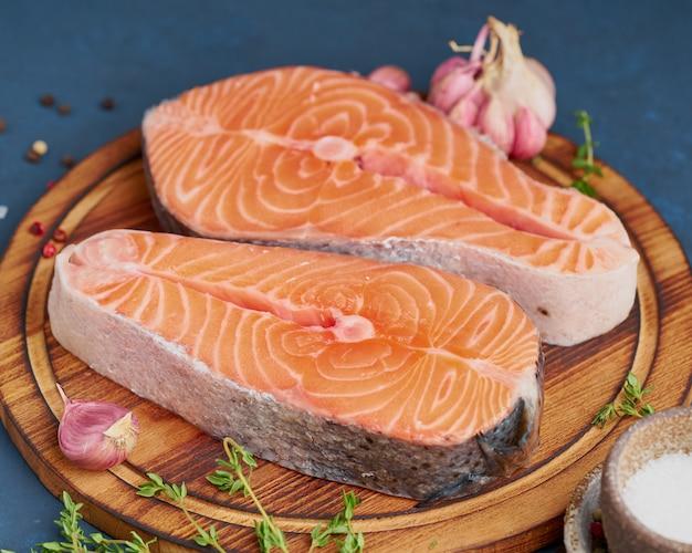 暗いテーブルの上のまな板の上の2つのサーモンステーキ、魚の切り身、大きなスライス部分。側面図