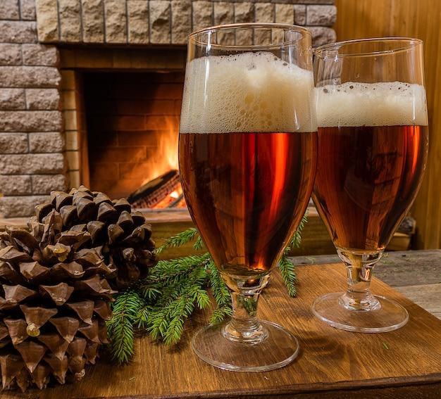2つのビールグラス、コーン、居心地の良い暖炉に対してクリスマスツリーブランチ。
