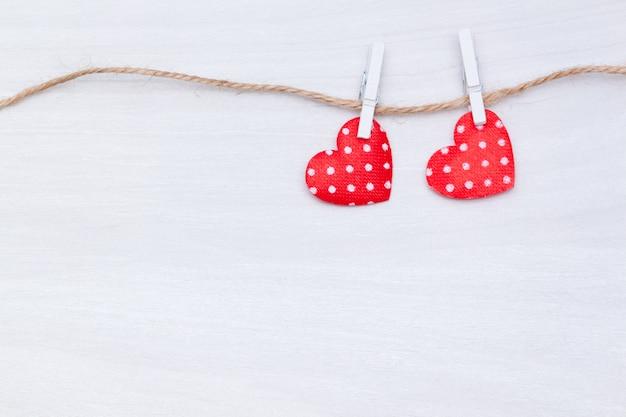 白い木製の背景上のスレッドに掛かっている2つの赤いハート。バレンタインデー、愛、結婚式のコンセプト。フラット横たわっていた、トップビュー。