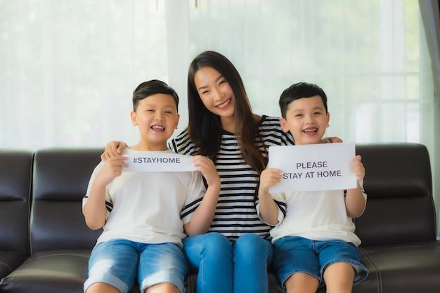 彼女の2人の息子を持つ美しい若いアジアのお母さんは、コロナウイルスを保護するために家に滞在する紙を表示します。