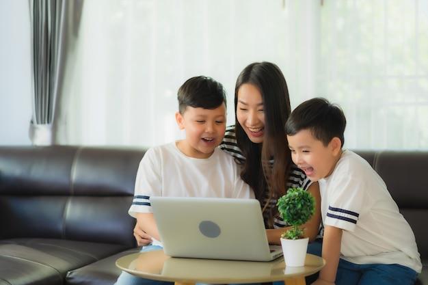 Красивая молодая азиатская мама женщины с 2 ее ноутбуком пользы сына или ноутбуком компьютера на диване