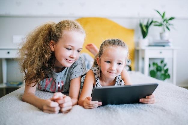 ベッドで横になっている2人の美しい妹とタブレット、スマートな技術を使用してスマートな子供たちの画面を見て