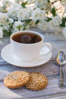 咲くジャスミンを背景に木製のテーブルに紅茶とゴマと2つのオートミールクッキーと白磁カップ。