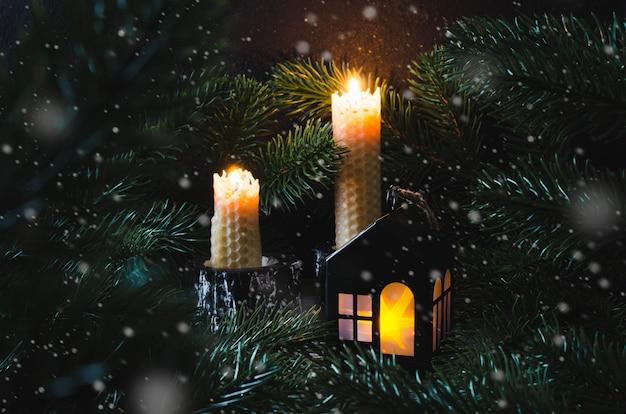 クリスマスのおもちゃの家とモミの中で2つのキャンドル。