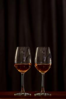カップルのために祝うために木製のテーブルの上にローズワインを2杯。