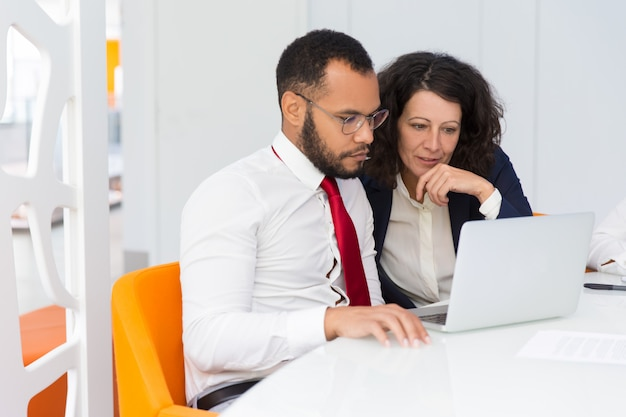 一緒にノートパソコンの画面を見ている2人の同僚