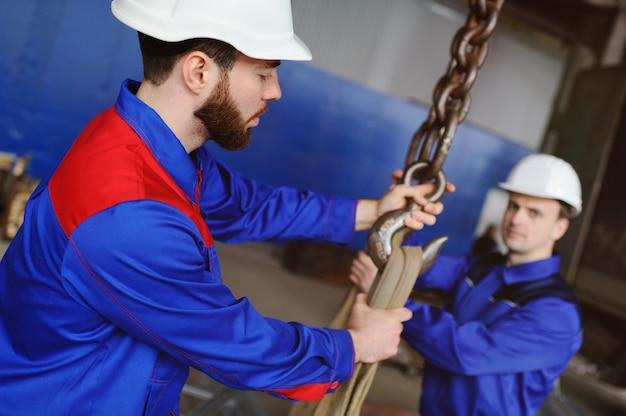 2人の労働者がクレーンフックに工業製品を積み込む