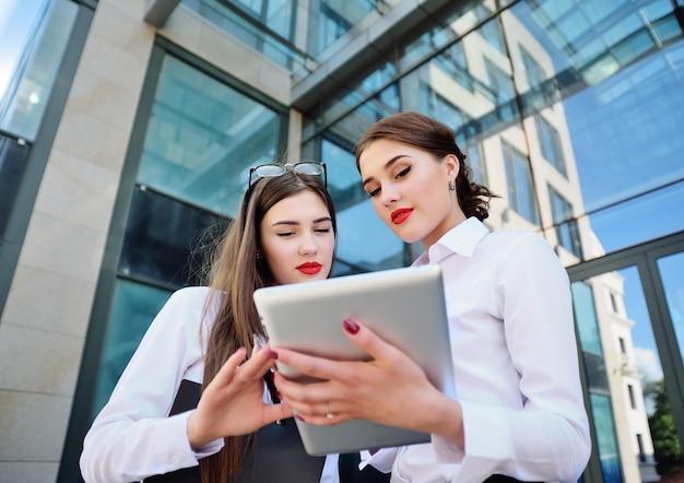 コンピューターのタブレットを見て話している古典的なオフィス服の2つの若いビジネス女性マネージャー。