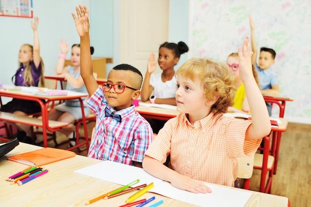2人の小さな男子生徒が手を上げて、中学校の教室での教師の課題に答えます
