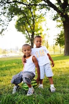 公園に笑みを浮かべて大きなスイカの上に座って2つの幸せな黒アフリカ系アメリカ人の男の子