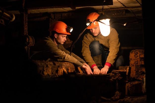 低いトンネルに座っている作業服と保護用のヘルメットを着た2人の若い男。鉱夫