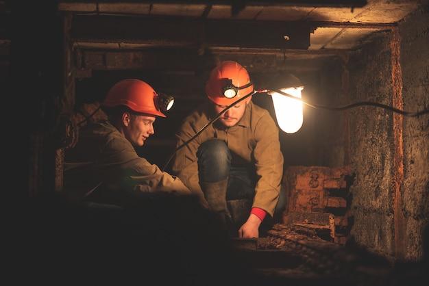 低いトンネルに座っている作業服と保護用のヘルメットを着た2人の若い男。鉱山の労働者