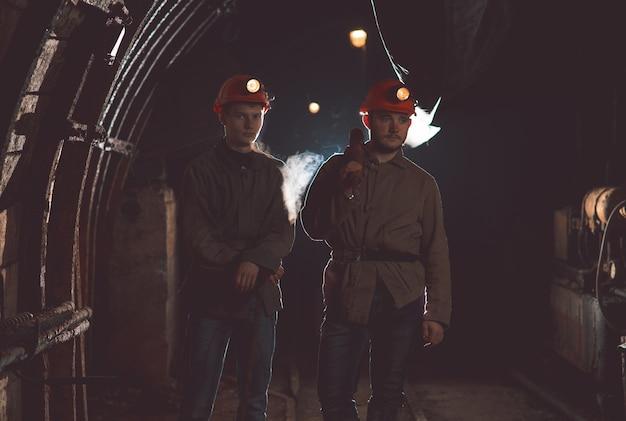 鉱山に立っている特別な服とヘルメットを着た2人の男。鉱夫