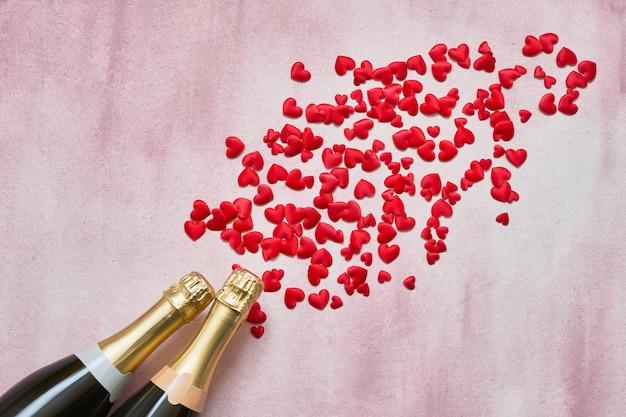ピンクの背景に赤と白の心を持つ2つのシャンパンボトル
