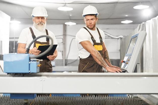 金属工場で一緒に働く2人の熟練したメカニック