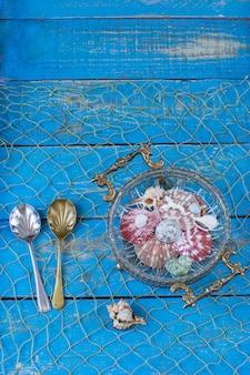 青い木製のテーブルの上に古い花瓶、その中にシェルがあり、シェルの形で2つの古いスプーンの隣にあります