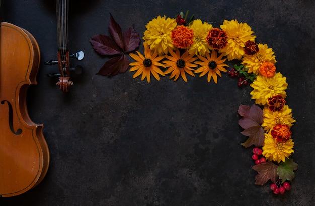 2つの古いバイオリンと明るい秋の花のパターン