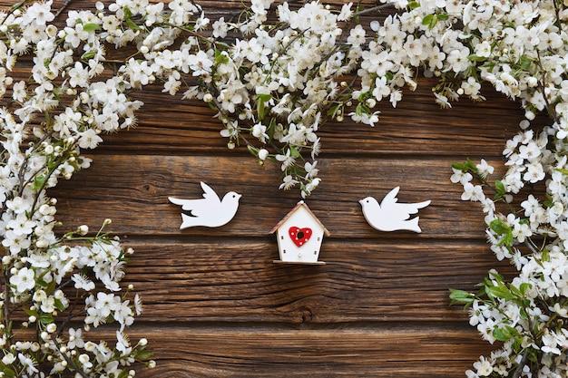 2つの木製の鳥と巣箱と白い開花桜の木の枝。