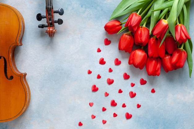 2つの古いバイオリン、赤いハート形の置物と赤いチューリップの花束。