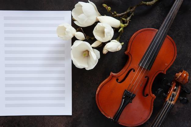 2つの古いバイオリンとメモ用紙に開花のマグノリア。上面図、クローズアップ。