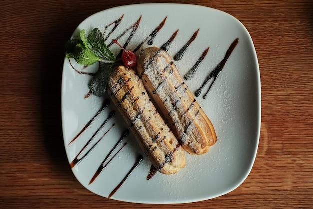 皿の上の2つの甘いフレンチエクレア。カフェで朝食をとる。木製のテーブルの背景