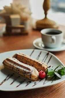 皿の上の2つの甘いフレンチエクレア。カフェで朝食をとる。木製のテーブル背景の側面図