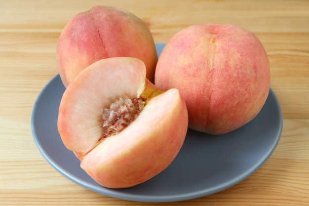 2 свежих зрелых плодоовощ персика целых и один персик отрезка на голубой плите служили на деревянном столе.