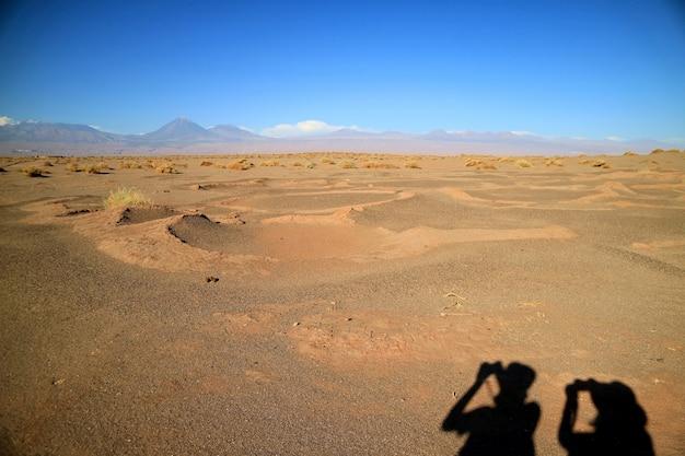 チリのアルデアデチュロール古代の村の地面に2人の観光客の影