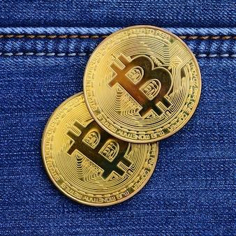 2つの金色のビットコインはブルージーンズ生地の上にあります。新しいバーチャルマネー。コインの形の新しい暗号通貨