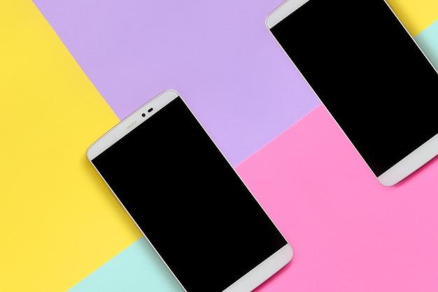 カラフルな質感の黒い画面を持つ2つの現代のスマートフォン