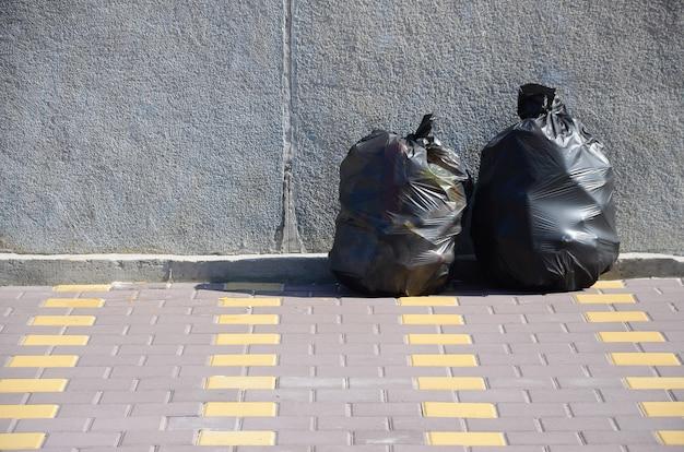 市のコンクリートフェンスでタイル張りの通り階に2つの黒いゴミ袋
