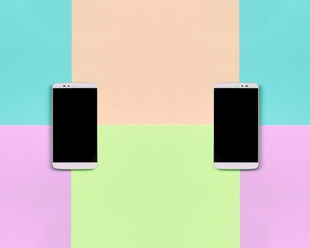 ファッションパステルピンク、ブルー、サンゴ、ライムの色の黒い画面を持つ2つの近代的なスマートフォン