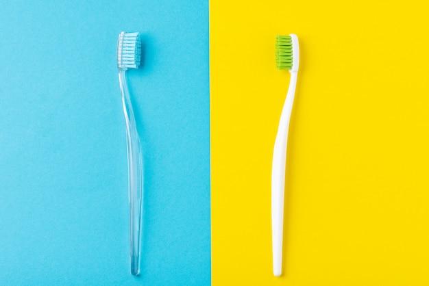 パステルブルーとイエローの2つのプラスチック歯ブラシ、フラットレイアウトスタイル