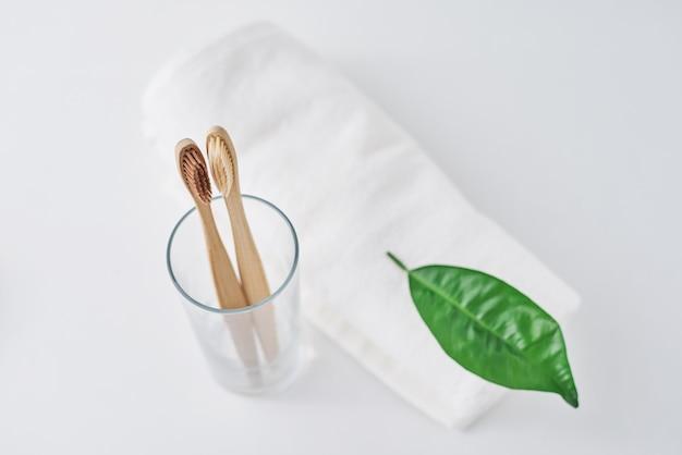 ガラスと白い背景の上のタオルで2つの木製竹エコフレンドリーな歯ブラシ。デンタルケアと廃棄物ゼロのコンセプト