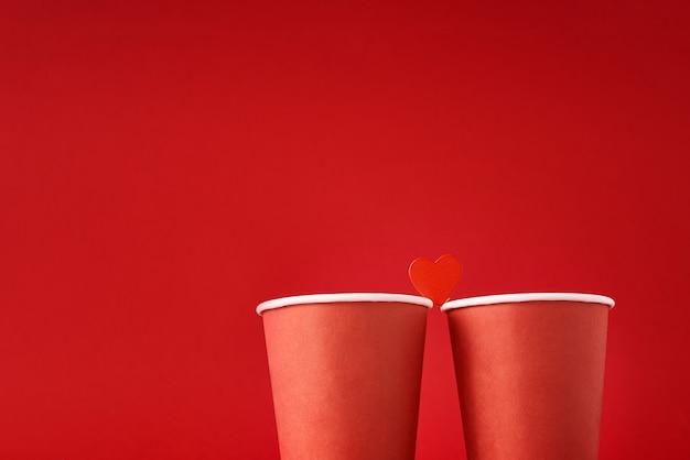 赤い表面に愛のカップルとして心で2つの赤いコーヒーカップ。バレンタインデーとロマンチックなコンセプト