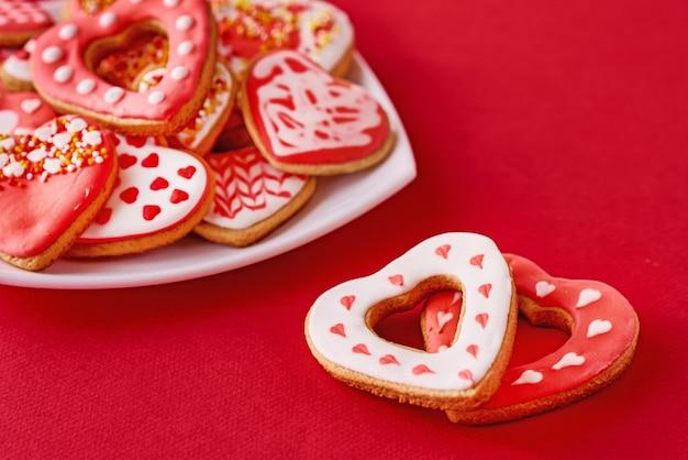 白いプレートにハート型のクッキーと赤い表面に2つのクッキーが飾られています。バレンタインデーの食べ物のコンセプト