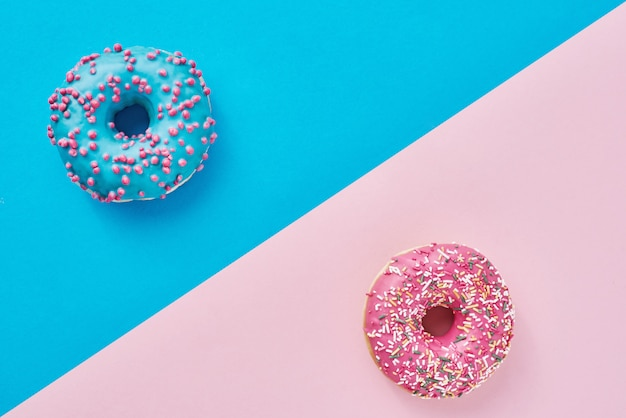 パステルピンクとブルーの背景に2つのドーナツ。ミニマリズムの創造的な食品の組成物。フラットレイスタイル