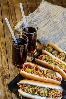 ピクルス、玉ねぎ、ケチャップ、マスタード、2つのソーダのアメリカンホットドッグ