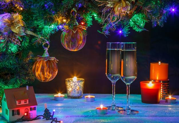 2つのシャンパングラス、キャンドルとクリスマスツリー