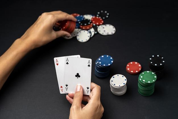 テーブルの上の2つのエースでチップと女性の手のスタック。ポーカーゲームのコンセプト
