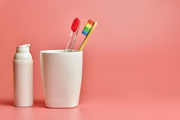 ピンクの背景に歯磨きで2つの歯ブラシ