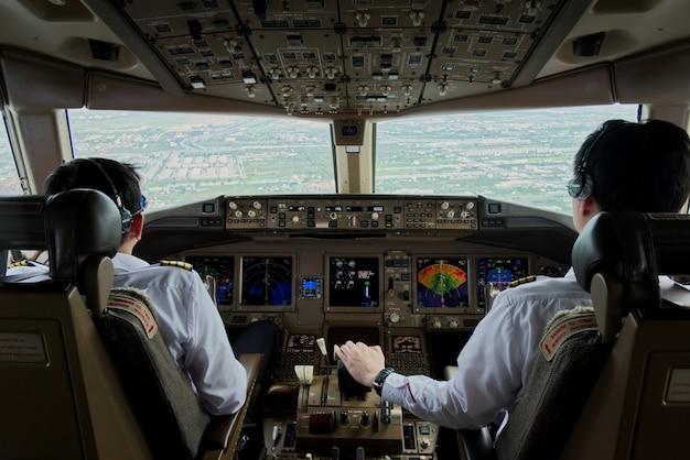 2人の旅客機パイロットが滑走路に向かって飛行機を制御しています。
