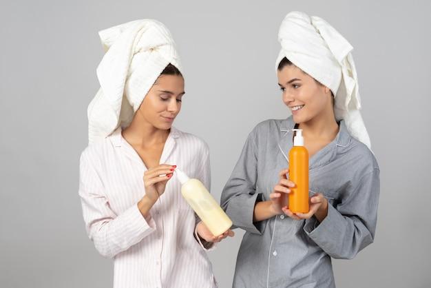 化粧品ボトルを保持している2人の女性の友人