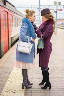 2人の友人が駅のプラットホームでコートに立っています。