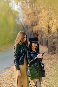 2つの居心地の良い若い女の子が秋の公園の道を歩いて、写真を作る