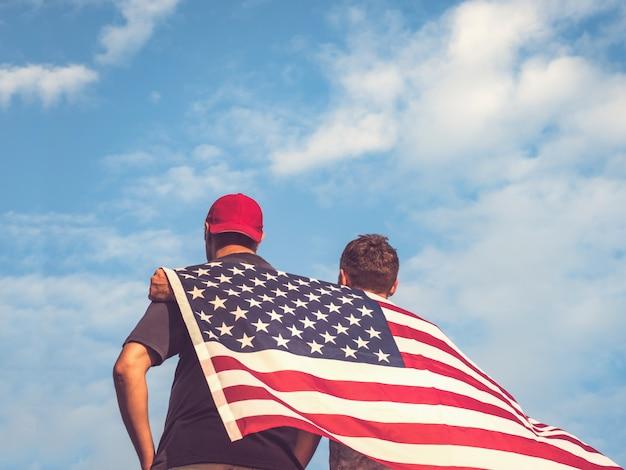 アメリカ合衆国の旗を保持している2人の男性