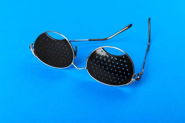 青い背景上のガラスの2つの異なる種類。医療コンセプト上面図。ピンホール黒眼鏡は疲れ目を白い背景で隔離のリラックスに役立ちます。クラシックファッション光学眼鏡