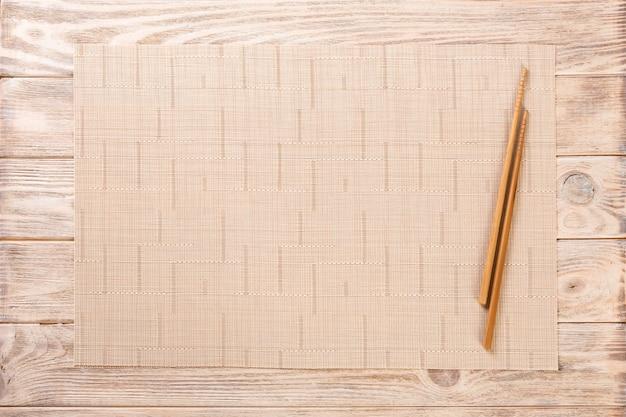 空の茶色の竹マットまたは木製プレートと寿司箸2本